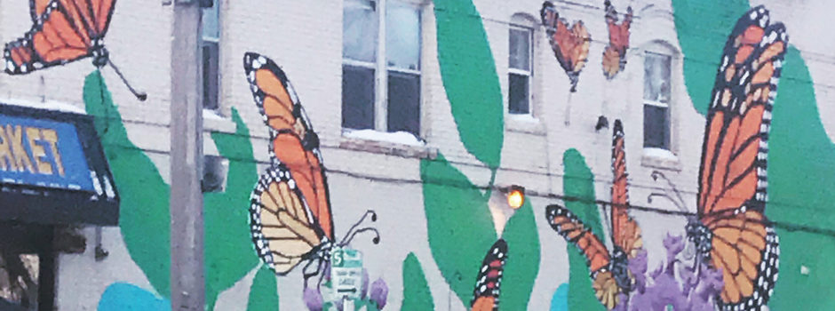 Colorful butterfly mural over brick wall
